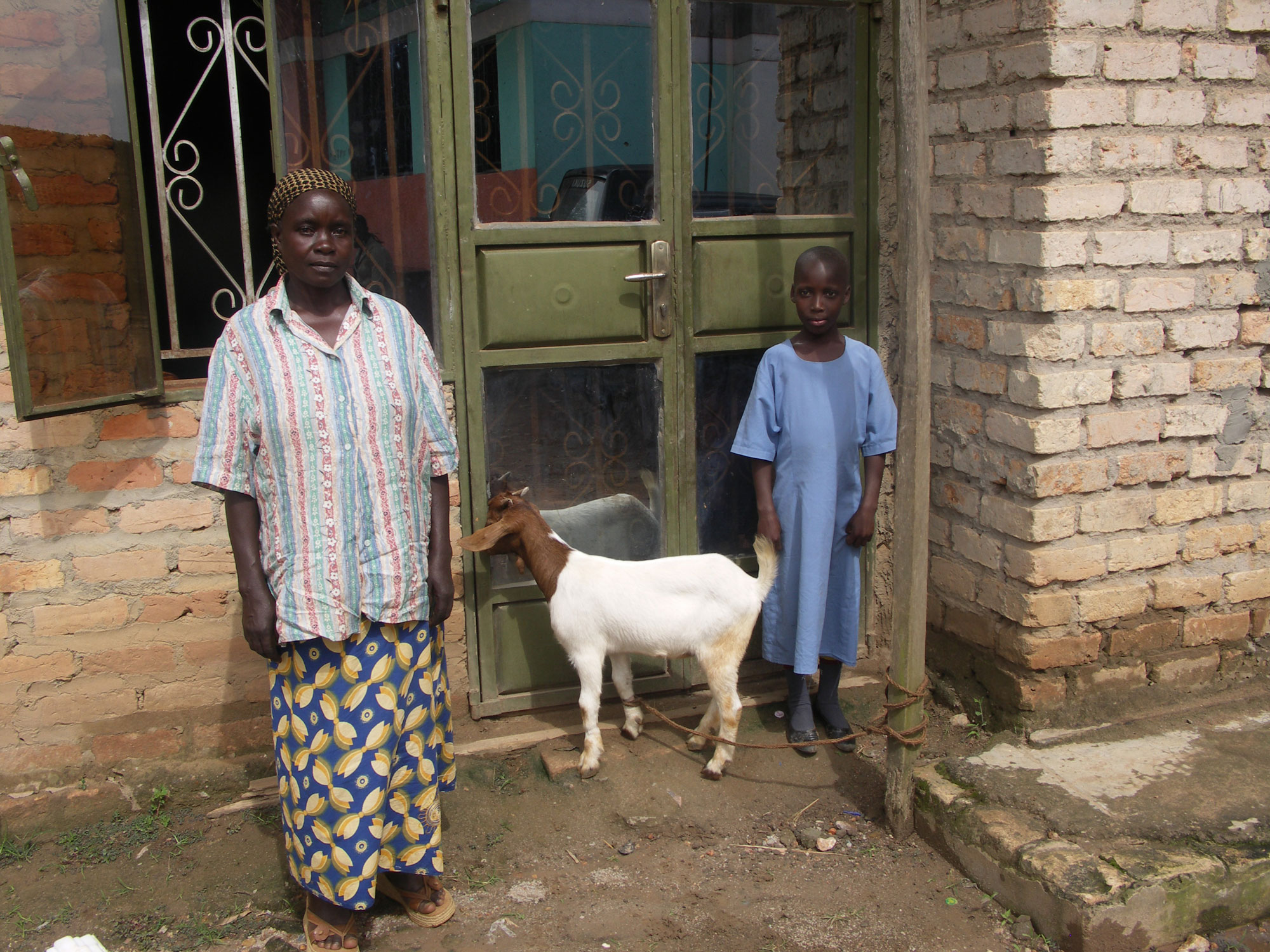 A child with her grandmother and the goat provided by a sponsor