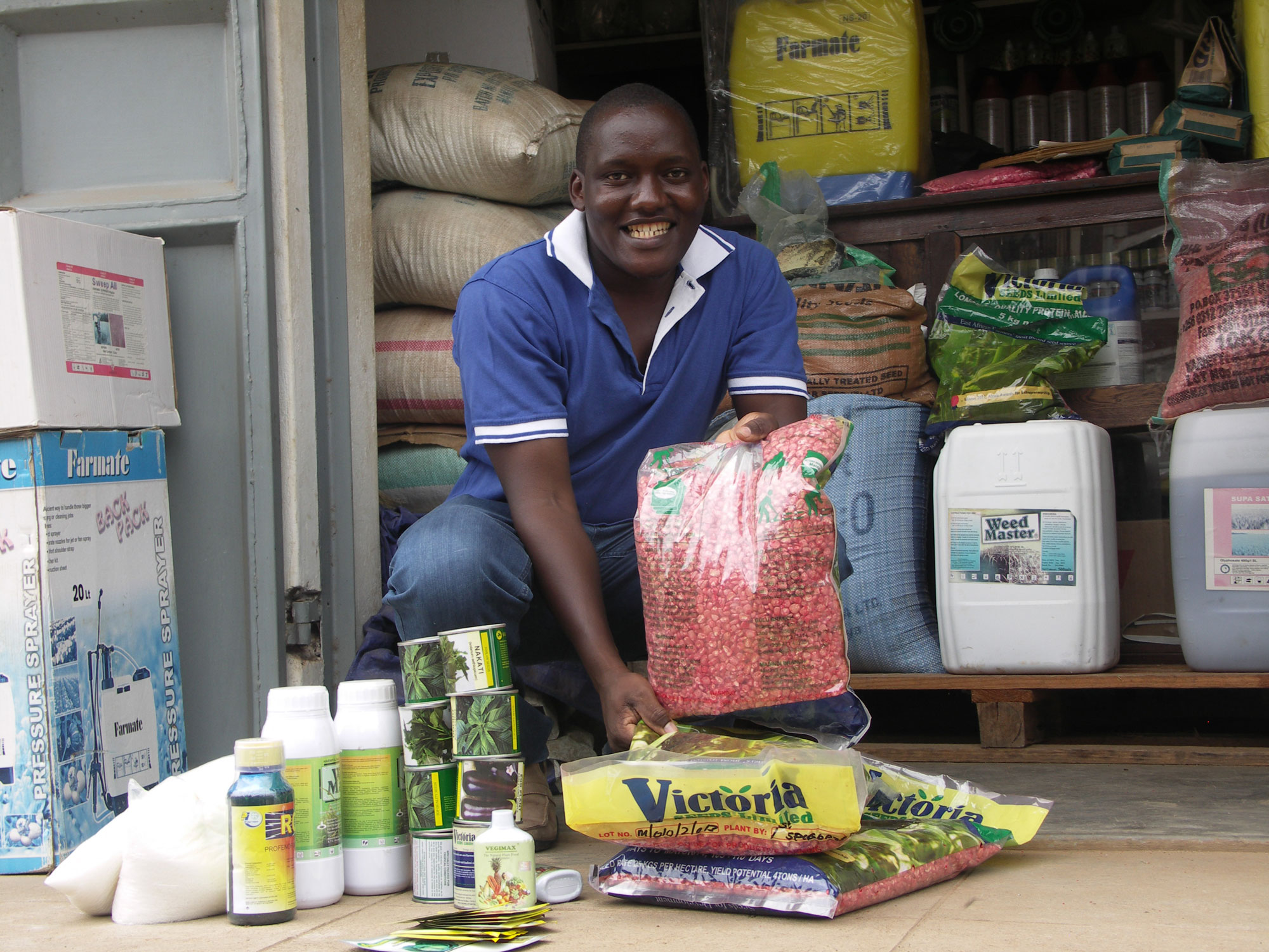 Micheal purchasing seeds and pesticides for distribution in the community